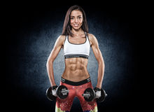 Athletic young woman doing workout with weights on dark backgrou Stock Image