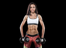 Athletic young woman doing workout with weights on dark background stock image