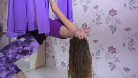 Athletic young woman doing yoga exersice with hammock in the home stock video