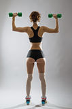 Athletic young woman with dumbbells in hand, rear view. Stock Image