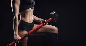 Athletic young woman engaged in gym with hammer and tire wheel. Concept workout fitness training.  stock image