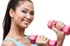 Athletic young woman exercises with dumbbells Royalty Free Stock Photography