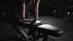 Athletic young woman in gym lifts metal weights. Exercise with weight on the bench, evening training. Close up. Athletic young woman in gym lifts metal weights stock video footage