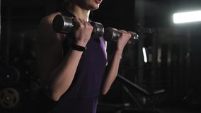 Athletic young woman in gym lifts metal weights. Exercise with weight training. Athletic young woman in gym lifts metal weights. Exercise with weight training stock footage