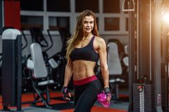 Athletic young woman after hard workout at gym. Fitness girl holds shaker with sportive nutrition. Athletic young woman after hard workout at gym. Fitness girl Royalty Free Stock Photo