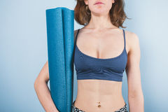 Athletic young woman holding a yoga mat Royalty Free Stock Photography