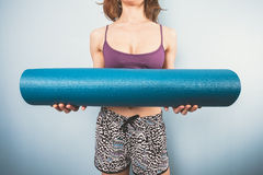 Athletic young woman holding a yoga mat Royalty Free Stock Images