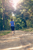 Athletic young woman jogging along a forest track Stock Photos