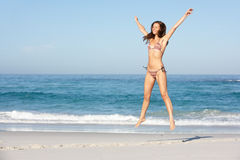 Athletic Young Woman Jumping On Beach Stock Image