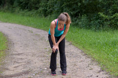 Athletic young woman with a knee injury. Pausing during her training running along a rural dirt track to clasp her knee in her hands Royalty Free Stock Photography