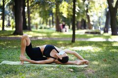 Athletic young woman in a medical protective mask, doing yoga in the Park. In the morning, women& x27;s training on a yoga Mat