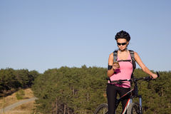 Athletic young woman on a mountain bike. With a phone in his hand Royalty Free Stock Photo