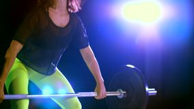 Athletic young woman, raises the barbell, does sit-ups with the barbell. At night, in the light of multicolored stock video