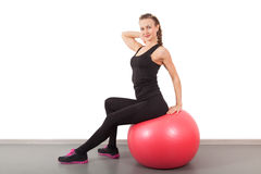 Athletic young woman on red ball Stock Image