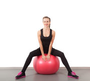 Athletic young woman on red ball Stock Photography