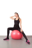 Athletic young woman on red ball Royalty Free Stock Photography