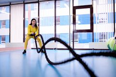 Athletic young woman with ropes for crossfit training in fitness gym royalty free stock photo