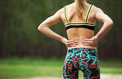 Athletic young woman rubbing the muscles of her lower back Stock Image