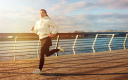 Athletic young woman running along river. Healthy lifestyle. Athletic beautifulyoung woman in black and white outfit running along river on a concrete. Healthy Stock Photos