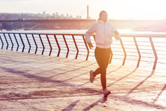 Athletic young woman running along river. Healthy lifestyle. Athletic beautifulyoung woman in black and white outfit running along river on a concrete. Healthy Royalty Free Stock Images