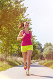 Athletic young woman running outdoors during autumn Stock Image