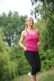Athletic young woman running outdoors Stock Image