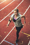 Athletic young woman running on track field. FIt young woman running on track field while listening to music Royalty Free Stock Photography