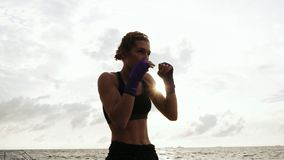 Athletic young woman shadow boxing by the sea against the sun. Beautiful female boxer training on the beach in the. Morning, throwing punches in slowmotion stock footage
