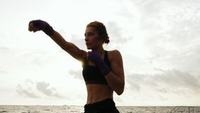 Athletic young woman shadow boxing by the sea against the sun. Beautiful female boxer training on the beach in the. Morning, throwing punches stock video footage