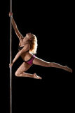 Athletic young woman show pole dance element Royalty Free Stock Photo