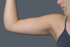 Athletic Young Woman Showing her Arm Muscle. Close up Athletic Young Woman Showing her Arm Muscle Against Grey Wall Background Stock Image