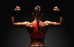 Athletic young woman showing muscles of the back. And hands on a isolated black background with clipping path Royalty Free Stock Photo