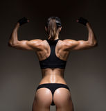 Athletic young woman showing muscles of the back Royalty Free Stock Photos