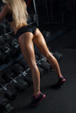 Athletic young woman showing muscles of the back. Sweaty woman having a break in a gym showing her well trained body, buttocks. Mesomorph Body Type. Girl's stock image