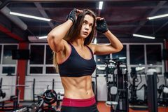 Athletic young woman showing muscles after workout in gym. stock photo