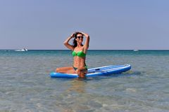 Athletic young woman sitting on a Board for SAP surfing in the sea in summer. royalty free stock photography