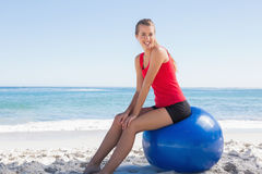 Athletic young woman sitting on exercise ball looking at camera Royalty Free Stock Images