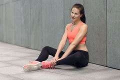 Athletic young woman sitting on the ground Stock Image