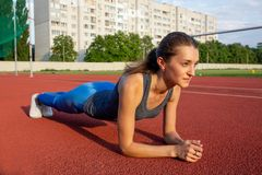 Athletic young woman in sport clothing doing plank exercise outdoor at the stadium royalty free stock photography