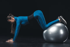 Athletic young woman in sportswear exercising with fitness ball Royalty Free Stock Images