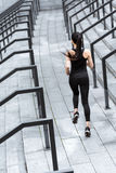 Athletic young woman in sportswear running on stadium stairs Royalty Free Stock Images