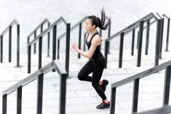 Athletic young woman in sportswear running on stadium stairs Stock Photography