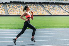 Athletic young woman in sportswear sprinting on running track stadium. Side view of athletic young woman in sportswear sprinting on running track stadium Royalty Free Stock Photography