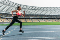 Athletic young woman in sportswear sprinting on running track stadium. Side view of athletic young woman in sportswear sprinting on running track stadium Royalty Free Stock Photos