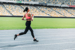 Athletic young woman in sportswear sprinting on running track stadium. Side view of athletic young woman in sportswear sprinting on running track stadium Royalty Free Stock Photo