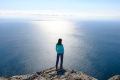 Athletic young woman standing on the rocky top of the mountain against the blue of sky and sea. Back to the camera Royalty Free Stock Image