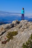 Athletic young woman standing on the rocky top of the mountain a Royalty Free Stock Image