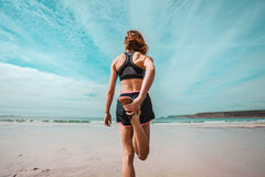 Athletic young woman stretching on the beach Stock Photos