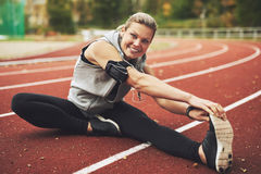 Athletic young woman stretching on track field Stock Photo