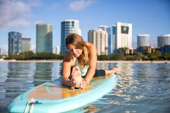 Athletic young woman in SUP Yoga practice front bend Pose in Ala Stock Photos